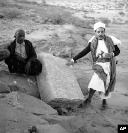 FILE - Two Yemenis stand near a column bearing ancient South Arabian script at the Awwam Temple, also known as the Mahram Bilqis in Marib, Yemen, in February 1957.