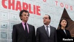 """El presidente francés, François Hollande (centro) y la ministra de Cultura, Fleur Pellerin (derecha) y el presidente del Institut du Monde Arabe, Jack Lang (L) posan frente a un rótulo que lee """"Yo soy Charlie""""."""