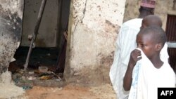 A child covers his nose inside a mosque where a suicide bomber killed over 20 worshipers in Maiduguri, Sept. 21, 2015.