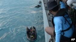 在爪哇海海域,印尼海军潜水员准备打捞亚航失事客机尾部残骸。
