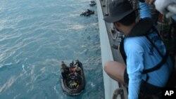 Індонезійські водолази готуються підняти частину літака на поверхню моря