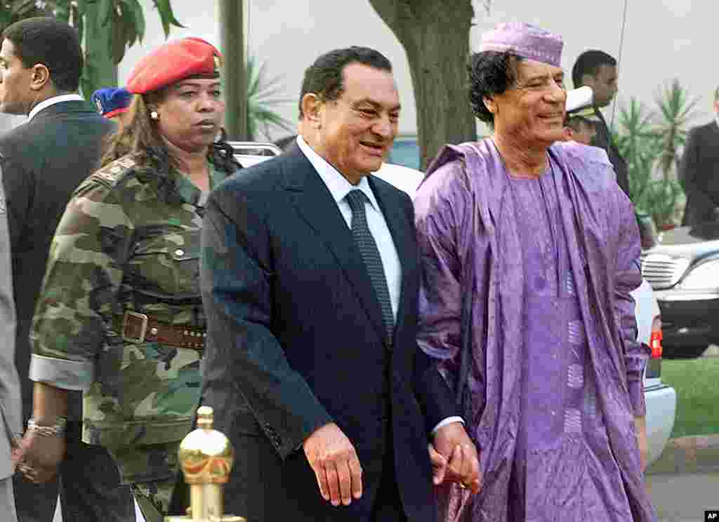 Egyptian President Hosni Mubarak, center, welcoming Libyan leader Moammar Gadhafi, right, who is guarded by a female bodyguard, left, upon his arrival at the Presidential Palace in Cairo, 21 July 2002.