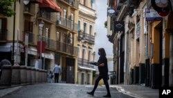 រូបឯកសារ៖ អ្នករត់តុម្នាក់លើកភេសជ្ជៈឆ្លងកាត់ផ្លូវមួយនៅក្រុង Seville ប្រទេសអេស្ប៉ាញ កាលពីថ្ងៃទី១១ ខែឧសភា ឆ្នាំ២០២០។