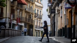 A waitress carries a tray across the road to a terrace bar in Seville, Spain, Monday, May 11, 2020. (AP Photo/Miguel Morenatti)