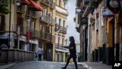រូបឯកសារ៖ អ្នករត់តុម្នាក់លើកអាហារឆ្លងថ្នល់មួយនៅក្រុង Seville ប្រទេសអេស្ប៉ាញ កាលពីថ្ងៃចន្ទ ទី១១ ខែឧសភា ឆ្នាំ២០២០។