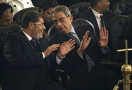 Mohamed Morsi, left, of Egypt's Muslim Brotherhood and Egyptian presidential hopeful Amr Moussa, right, at the Coptic cathedral in Cairo, January 6, 2012
