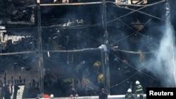 Bomberos trabajan en la bodega que se incendió el viernes en el distrito Fruitvale, de Oakland, California.