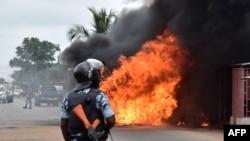 Un officier de police ivoirien se tient près d'un bus en feu à Abidjan, le 10 septembre 2015.