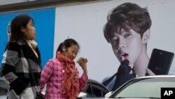 Perempuan China berjalan melewati iklan yang menampilkan idola remaja, Lu Han, yang dikenal sebagai Justin Biebernya China di Beijing, China, 21 Oktober 2017. China berusaha menahan popularitas para selebritis untuk menanamkan nilai-nilai nasionalisme pada anak muda China.