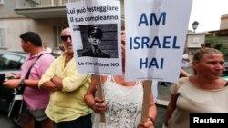 """Una mujer eleva los carteles de protesta contra Erich Priebke que dicen """"El pueblo judío vive"""" y otro que dice """"Él puede celebrar su cumpleaños, sus víctimas no""""."""