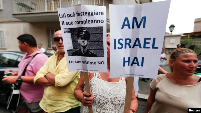 A woman holds signs reading, 'The Jewish People Live' (R) and 'He can celebrate his birthday, his victims no' during a protest against convicted former Nazi SS captain Erich Priebke in Rome, July 29, 2013.