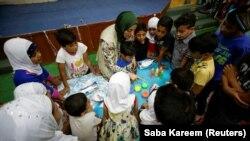Ibu tunggal Irak Marwa Raed Taha, yang bekerja sebagai sukarelawan, mengajar anak-anak, di penampungan Amiriya di Baghdad, Irak, 21 April 2021. (Foto: REUTERS/Saba Kareem)