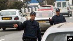 Des policiers contrôlent des véhicules à une barrière, à Alger. 18 mars 2005.