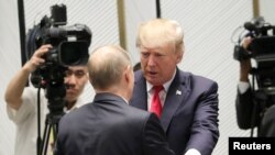 """U.S. President Donald Trump and Russian President Vladimir Putin talk before a session of the APEC summit in Danang, Vietnam, Nov. 11, 2017. """"We seem to have a very good feeling for each other,"""" Trump said about his relationship with Putin."""