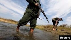 克钦独立军士兵淌过一条溪流,前往拉咱前线。(2013年2月4日资料照)