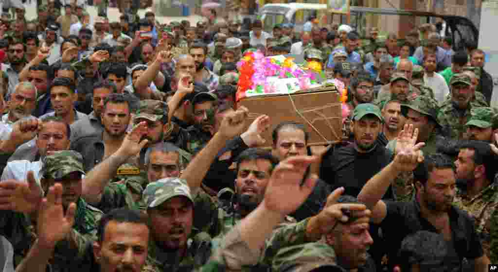 Mourners chant slogans against the Islamic State group as they carry the flag-draped coffins of three members of the Peace Brigades, a Shi'ite militia group loyal to Shi'ite cleric Muqtada al-Sadr during their funeral processions in Najaf, May 27, 2015.