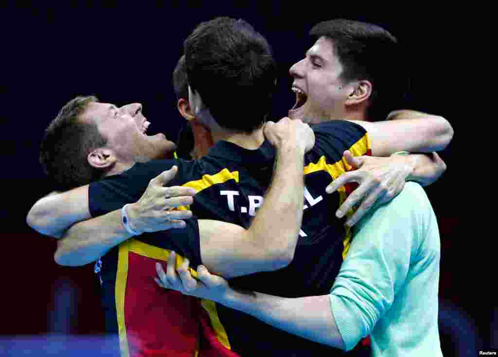 Germany's Dimitrij Ovtcharov (R) celebrates winning with his teammates in the men's table tennis match against Hong Kong.