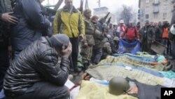 Activistas junto a los cuerpos de manifestantes muertos tras choques con la policía en la Plaza de la Independencia, en Kiev.