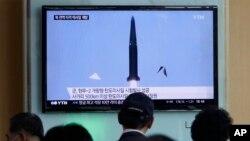 Warga menonton berita televisi yang menunjukkan uji coba rudal Korea Utara di stasiun kereta api Seoul, Korea Selatan, 3 Juni 2015. (AP/Ahn Young-joon)