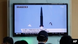 People watch a TV news program showing South Korea's missile test at Seoul Railway Station in Seoul, South Korea, June 3, 2015.