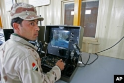FILE - An Iraqi soldier practices using a robot during a bomb disposal training for the Iraqi security forces at a Besmaya range complex just outside Baghdad, Nov. 17, 2008.