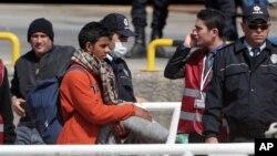 Los migrantes son escoltados uno por uno de los barcos a un centro de registración en la isla griega de Lesbos.