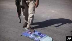 A rebel fighter steps over a calendar with Moammar Gadhafi's picture at a checkpoint in Tripoli, Libya, July 30, 2011