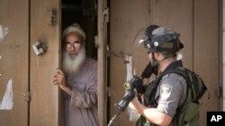 Warga Palestina menutup tokonya dalam bentrokan antara tentara Israel dan demonstran Palestina di kota al-Ram, Tepi Barat (22/10). (AP/Majdi Mohammed)