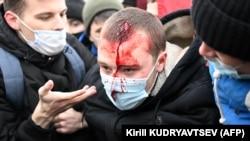 Un homme blessé est aidé par d'autres manifestants dans le centre de Moscou le 23 janvier 2021.