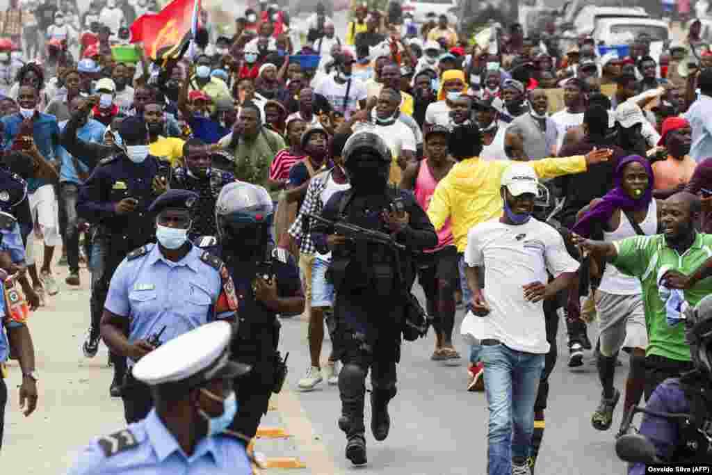 Polícias correm entre manifestantes durante o protesto contra o aumento do custo de vida, a corrupção em todo o país e para exigir a realização de eleições locais