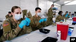 FILE - U.S. Army health specialists fill syringes with the Pfizer COVID-19 vaccine, in Miami, Florida, March 9, 2021.