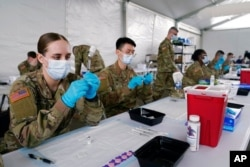 FILE - Army health specialists fill syringes with the Pfizer COVID-19 vaccine in Miami, Florida, March 9, 2021.
