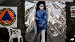 A paramedic wearing a mask gets out of a tent set up by the Italian Civil Protection outside the emergency ward of the Piacenza hospital, northern Italy, Feb. 27, 2020.