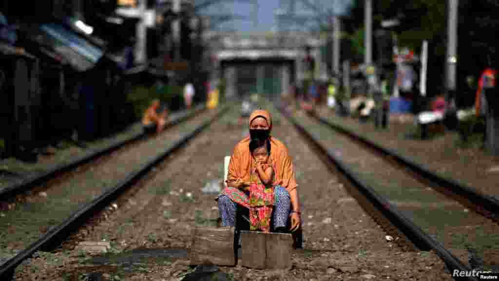 인도네시아 정부가 신종 코로나바이러스 감염증(COVID-19) 확산 방지를 위해 대규모 사회적 통제를 가하는 조치를 내린 가운데 수도 자카르타의 열차 선로 사이에서 모자가 카메라를 응시하고 있다.