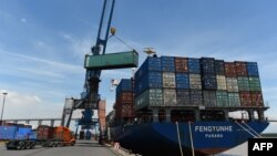FILE - Containers are transferred from a truck to a cargo ship at the international cargo terminal of a port in Hai Phong, Vietnam, Aug. 12, 2019.