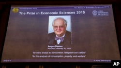 Professor Angus Deaton, winner of the 2015 Sveriges Riksbank Prize in Economic Sciences in Memory of Alfred Nobel, as the Permanent Secretary for the Royal Swedish Academy of Sciences addresses a press conference to announce the winner of the prize, Oct.