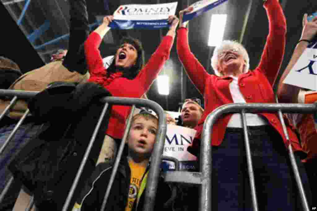 A small boy looks on as supporters cheer as Republican presidential candidate, former Massachusetts Gov. Mitt Romney spoke at a campaign rally at Skyline High School in Idaho Falls, Idaho, Thursday, March 1, 2012. (AP Photo/Gerald Herbert)
