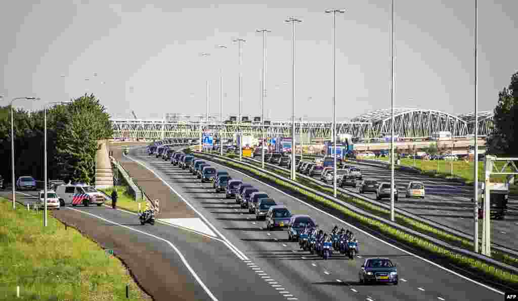A convoy of hearses carry the remains of the victims of the Malaysia Airlines flight MH17 plane crash from an airbase in Eindhoven to Hilversum, The Netherlands, drives through Waardenburg after a Dutch Air Force C-130 Hercules plane and an Australian Royal Air Force C17 transporting the remains arrived from Kharkiv, Ukraine.