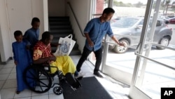 Ali Said, of Somalia, leaves a center for refugees with his two sons, as refugee caseworker Mohamed Yassin, right, holds open the door, July 6, 2017, in San Diego. Said, whose leg was blown off by a grenade, says he feels unbelievably lucky to be among the last refugees allowed into the United States before stricter rules kick in as part of the Trump administration's travel ban.