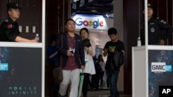 Attendees walk past security guards as they pass by the Google booth at the Global Mobile Internet Conference in Beijing, China, April 29, 2016.