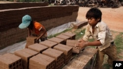 Cambodian children prepare bricks to dry under the sun light at a brick factory in Chheuteal village, Kandal province, some 27 kilometers (17 miles) north of Phnom Penh, Cambodia, Monday, May 2, 2011. Brick production is increasingly needed in…