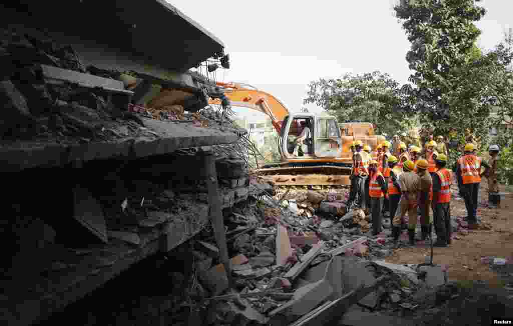 Rescuers search for survivors at the site of a collapsed building, Canacona, India, Jan. 5, 2014.