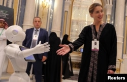 FILE - Aurore Chiquot of SoftBank Robotics Europe extends her hand to a robot during the Future Investment Initiative conference in Riyadh, Saudi Arabia, Oct. 25, 2017.