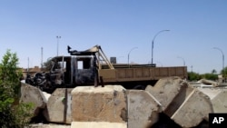 File - Military truck damaged in clashes between Islamic State fighters and Iraqi security forces at a military base north of Baghdad.