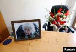 A photograph of late Nancy Hatch Dupree, an American historian, and a bouquet of flowers are seen in her office after she passed away, in Afghanistan Centre at Kabul University (ACKU), in Kabul, Sept. 10, 2017.