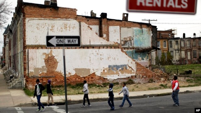 A group of boys walk past a partially collapsed row house in Baltimore, Maryland, Apr. 4, 2013. The U.S. Census Bureau estimates that 20 percent of American children are impoverished.