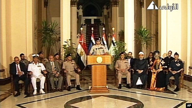 Lt. Gen. Abdel-Fattah el-Sissi, center, flanked by military and civilian leaders addresses the nation on Egyptian state television, July 3, 2013.
