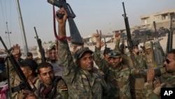 伊拉克軍隊高舉武器慶祝勝利。