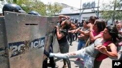 Des manifestants font face aux policiers anti-émeute à Valencia, Venezuela, le 28 mars 2018.