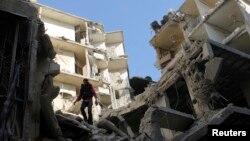 Čovek stoji na uništenoj zgradi u četvrti Alepa - Sukari, posle vazdušnog napada snaga pod kontrolom predsednika Bašara al-Asada